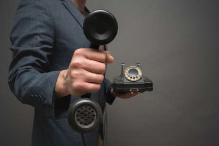 Rotary phone handset in man hand close up on gray background.