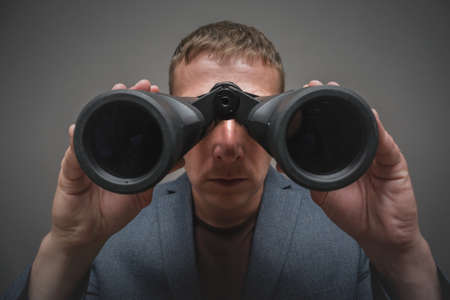 Serious man is looking through a binoculars in hands close up.