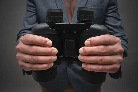 A binoculars in male hands close up.