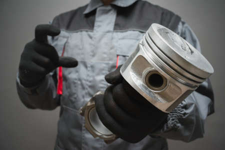A car mechanic is holding and old car engine piston close up on gray background. Фото со стока