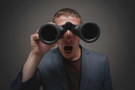 Shocked man is looking through a binoculars close up.