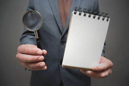 Magnifying glass and blank page notepad in the businessman hands close up on gray background. Фото со стока