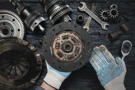 Old car clutch disk in car service worker hands close up on black table background. Фото со стока
