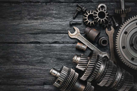A car gearbox spare parts and wrenches on black background with copy space. Фото со стока