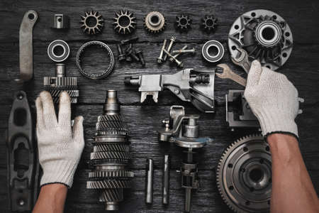 Car gearbox spare parts and car service worker hands with wrenches on the black flat lay background. Фото со стока