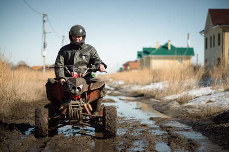 Biker riding quad bike on dirty countryside road.