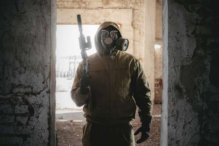 Soldier in the gas mask and with rifle in danger zone. Фото со стока