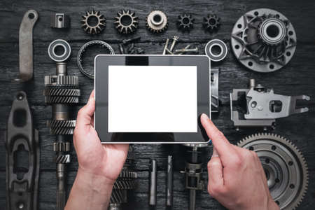 Car service worker is holding a blank screen digital tablet above spare parts background. Car spare parts order online concept.