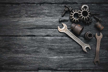 Cogwheels, nuts and wrenches on black flat lay workbench background with copy space.