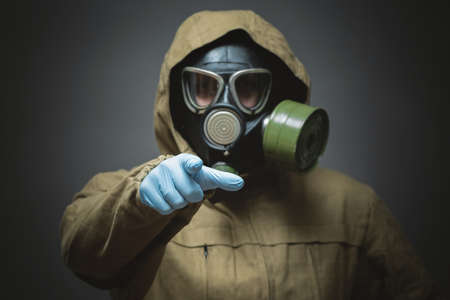 Man in gas mask is showing ahead by his index finger close up on gray background. Фото со стока