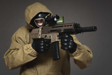 Soldier in gas mask with airsoft rifle on gray background.