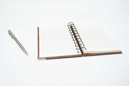 Blank page notepad and pen on the white table background.