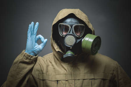 Man in gas mask is showing an Ok gesture by his hand close up on gray background. Фото со стока