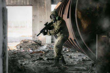 Soldier in gas mask and with rifle in the abandoned building.