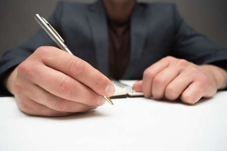 Businessman with pen is sitting by the desk close up.