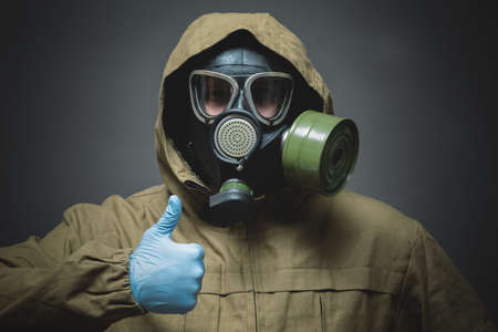 Man in gas mask is showing thumbs up gesture by his hand close up on gray background.