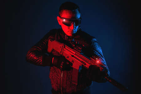 Futuristic soldier with a rifle in neon lights concept.