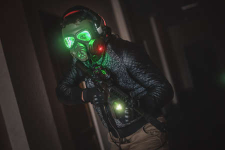 Futuristic soldier in the gas mask with a rifle in the dark hall.
