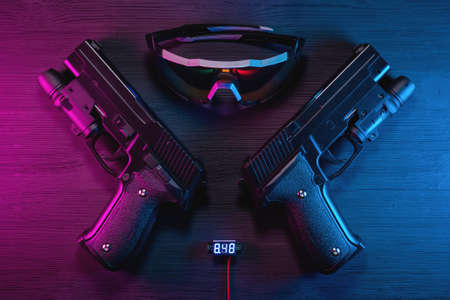 Toy guns and glasses on the black table flat lay background. Cyberpunk abstract concept background. Фото со стока