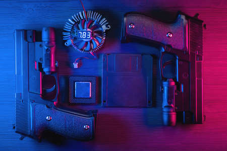 Floppy disk data, cpu chip, guns on black table flat lay background in the neon lights.