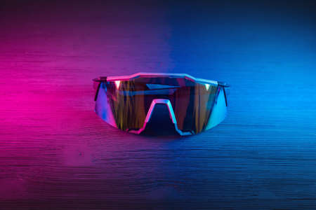Sport glasses on the table close up in neon lights background.