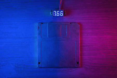 A floppy disk diskette in the neon lights on the black table flat lay background. Фото со стока