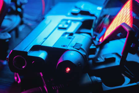 Toy guns and glasses on the black table close up background. Cyberpunk abstract concept background.