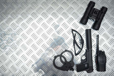 Toy gun, binoculars, bracelets and radio on the metal table background. Secret service concept background.