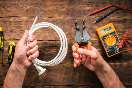 Cable stripper in electrician hands top view background.