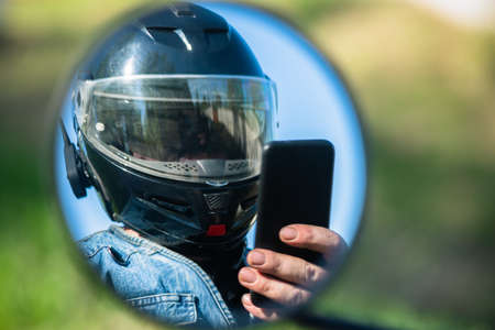Motor biker reflection in the mirror which is using a mobile phone close up.