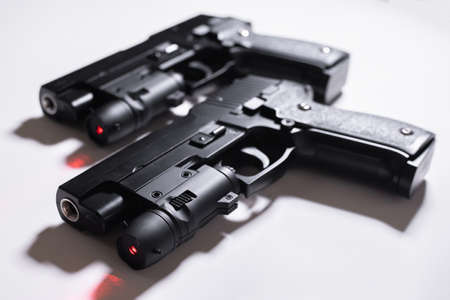Pair of black toy guns with laser aim on a white background.