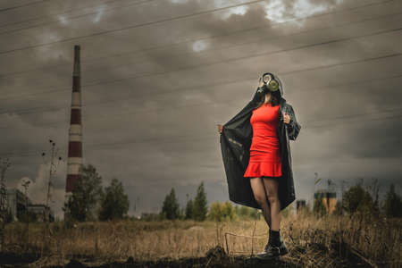 Woman in gas mask, red dress and in the raincoat is standing on the smoking chimney background. Фото со стока