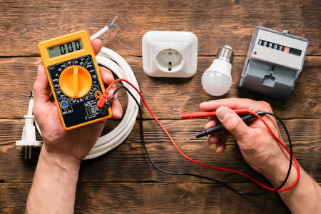 Electrician is holding in hands a multimeter on wooden workbench with various electrical equipment background. Фото со стока