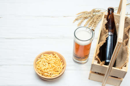 Light beer in the drinking glass, potato chips and bottle in the wooden box on the white table background.