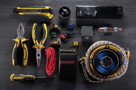 A car audio equipment and work tools on the black wooden table background. Car radio installation service concept. Stockfoto