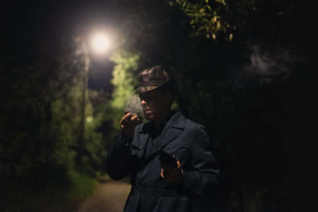 Detective man in the hat and coat with a gun is smoking a smoking pipe in the dark park.