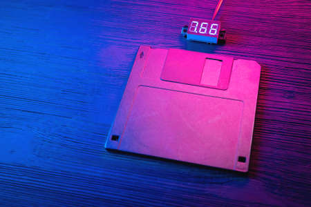 A floppy disk diskette in the neon lights on the black table background.
