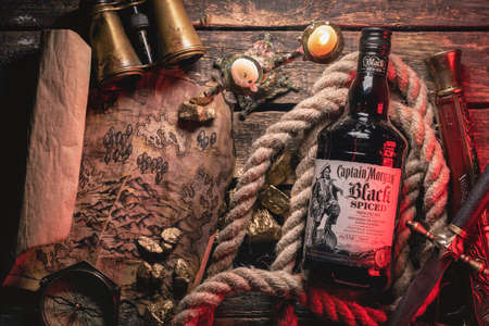 Moscow, Russia 25 June 2020: Luxury rum the Captain Morgan black spiced on the old wooden table background.