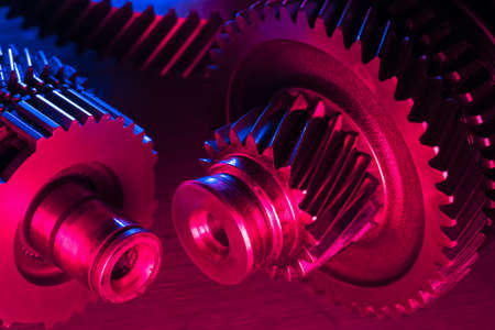 Disassembled car gearbox parts close up in the neon lights.