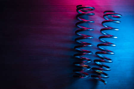 An old car coil suspension spring on the workbench background with copy space.