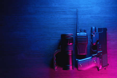 Spy secret service agent desk table concept background. Gun, radio and flashlight on the neon background with copy space. Banque d'images