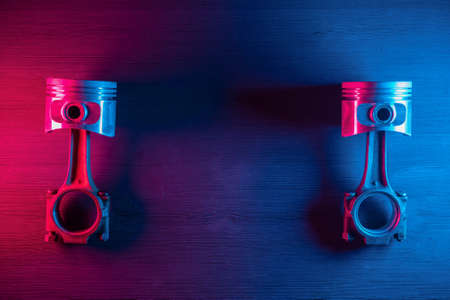 Old car engine pistons with connecting rod on the car service workbench background in the neon lights.