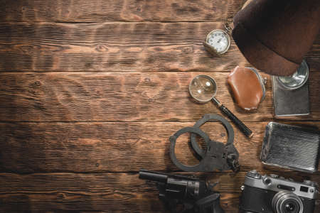 Spy detective agent equipment and accessories on the wooden desk background with copy space.