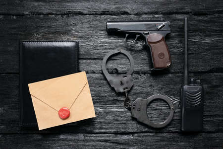A top secret letter and detective agent accessories on the black desk background.