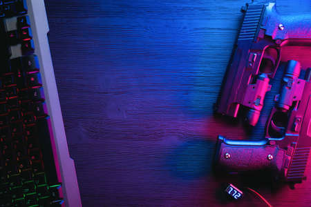 A two toy guns and computer keyboard on the black table background with copy space in the neon lights. Banque d'images