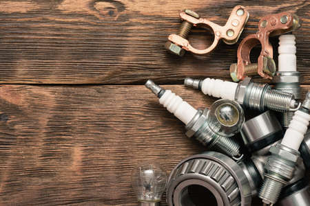 A car spark plug and other spare parts on the wooden workbench background with copy space.