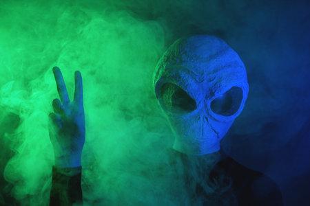 Alien is showing victory gesture on dark background.