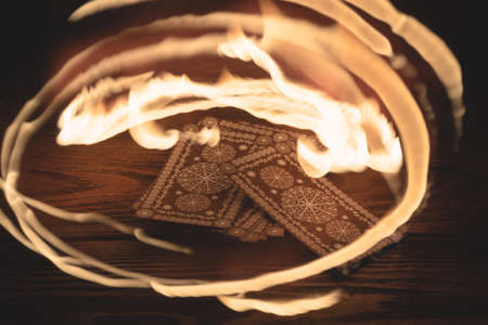 Tarot cards deck and fire flame around close up.