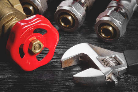 Adjustable wrench and red water valve close up. Plumbing background. 写真素材