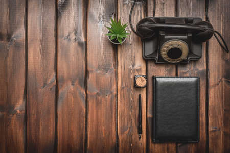Leather book, rotary phone, inkwell and quill pen on the brown wooden desk flat lay background with copy space.